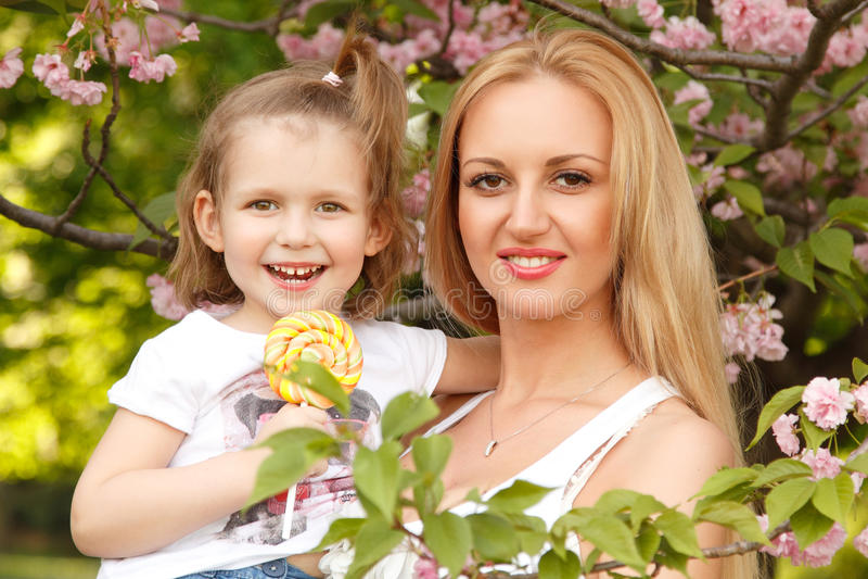 La mère heureuse avec la petite fille lèche l'outdoo de parc de ressort de sucrerie photographie stock