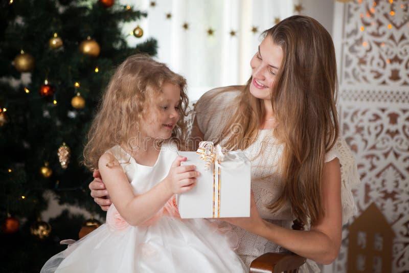 La mère heureuse dans la veste blanche donne le cadeau à une fille sur Noël images stock