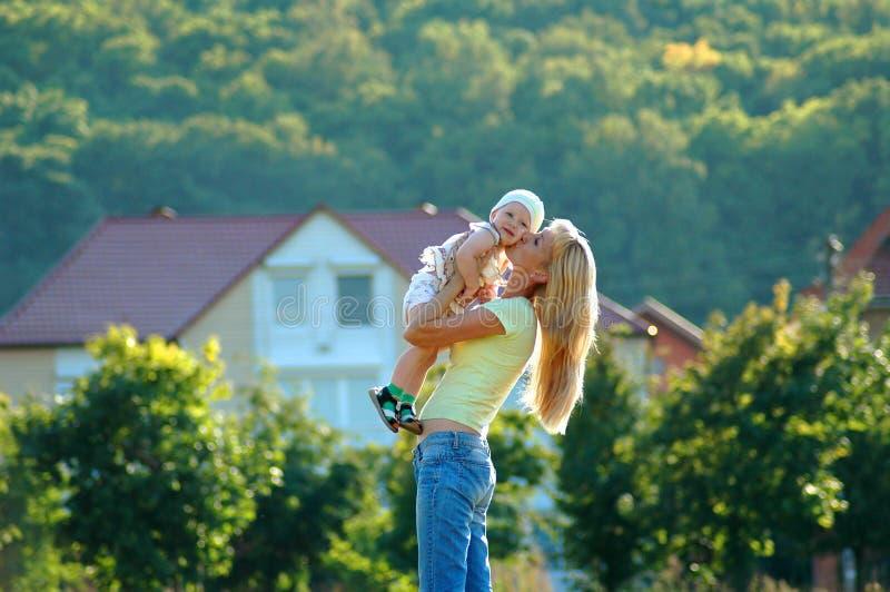 La mère heureuse embrasse l'enfant image stock