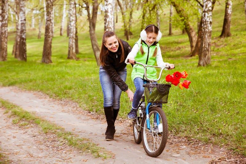 La mère heureuse enseigne sa fille à monter un vélo en parc photographie stock