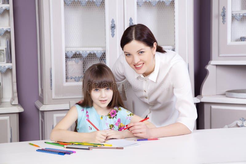La mère heureuse enseignent sa fille à peindre image stock