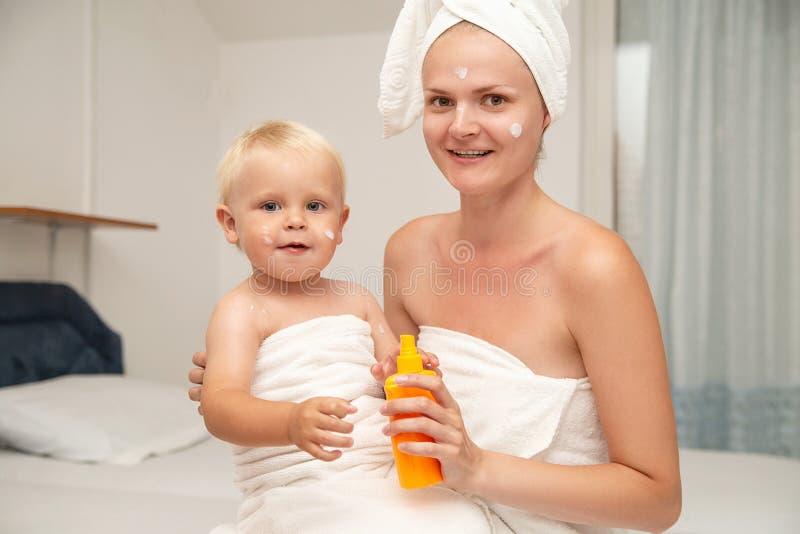 La mère heureuse et le bébé infantile en serviettes blanches après s'être baigné appliquent la protection solaire ou après lotion photos libres de droits