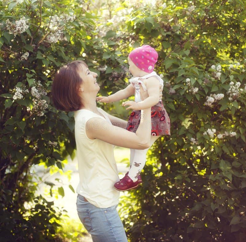 La mère heureuse joue avec l'enfant pendant l'été photographie stock