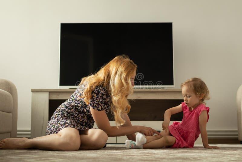 La mère interroge la petite fille au sujet de sa douleur de genou Il blesse photo libre de droits