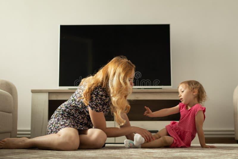 La mère interroge la petite fille au sujet de sa douleur de genou Il blesse images libres de droits