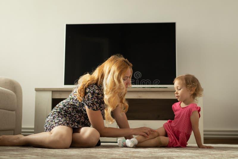 La mère interroge la petite fille au sujet de sa douleur de genou Il blesse image stock