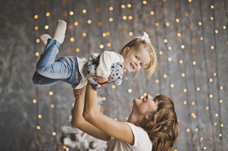 La mère jette la fille sur le fond des lumières de scintillement photos libres de droits