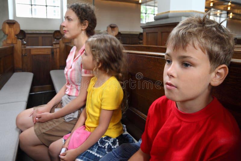 La mère, le descendant et le fils s'asseyent sur le banc dans l'église photographie stock