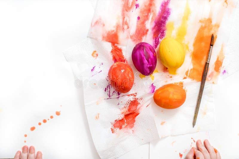 La mère, le père et le fils peignent des oeufs La famille heureuse se préparent à Pâques images stock