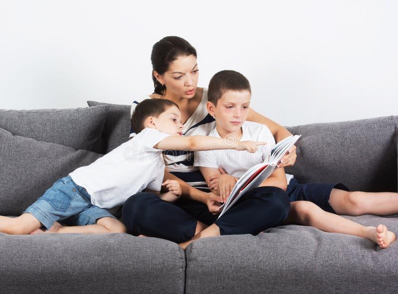La mère lit un livre intéressant avec ses fils du sofa images stock