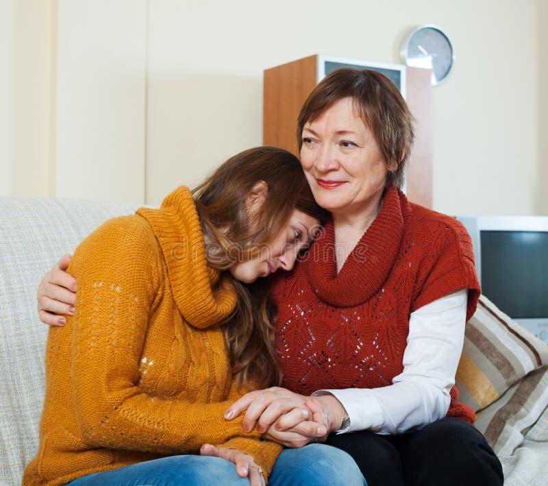 La mère mûre donne la consolation à la fille adulte pleurante images stock