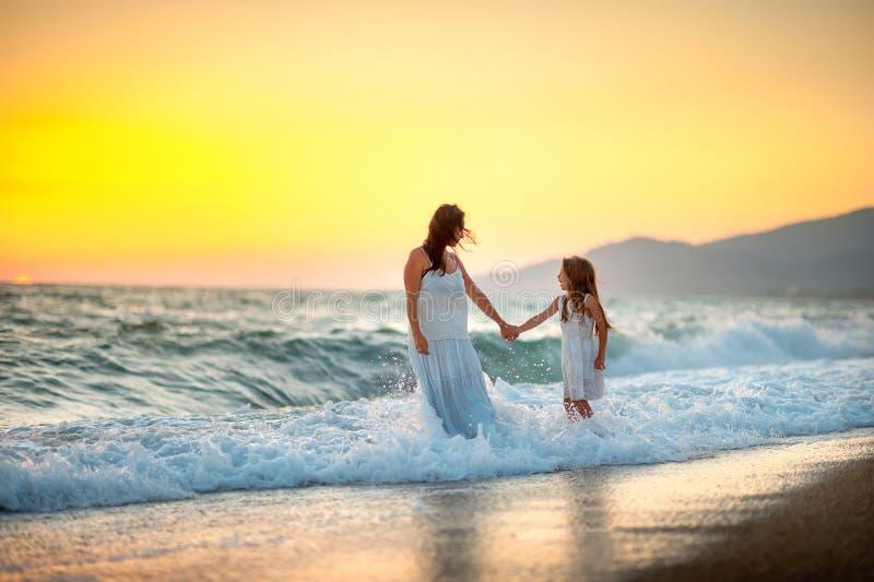 La mère marche avec sa fille sur la plage au coucher du soleil image libre de droits