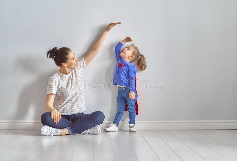 La mère mesure la croissance de l'enfant images stock