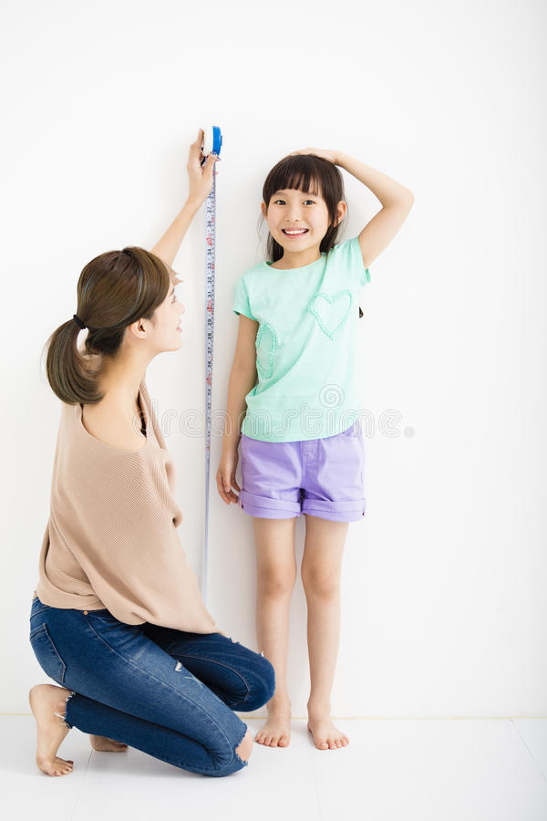 La mère mesure la croissance de sa fille photo stock