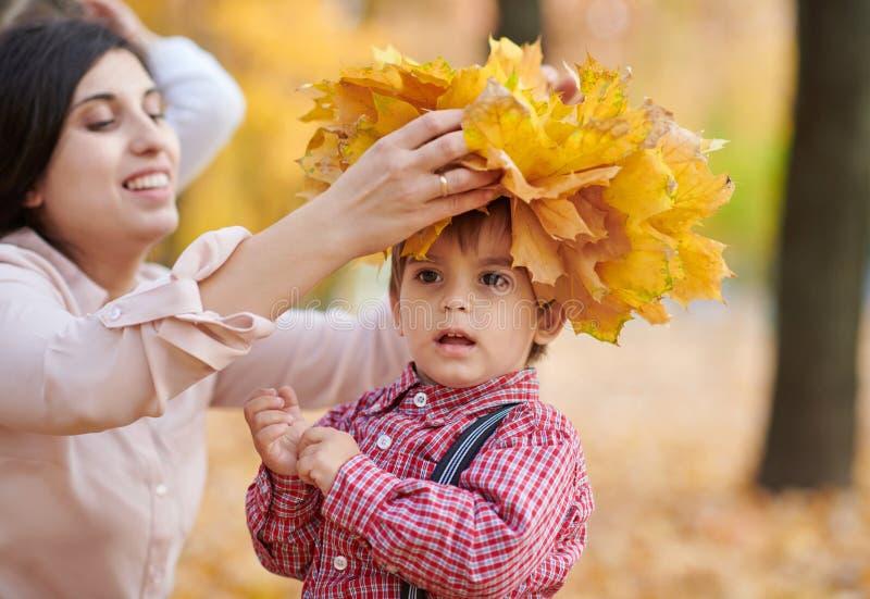 La mère met les feuilles tombées jaunes sur la tête de fils La famille heureuse est en parc de ville d'automne Enfants et parents photographie stock libre de droits