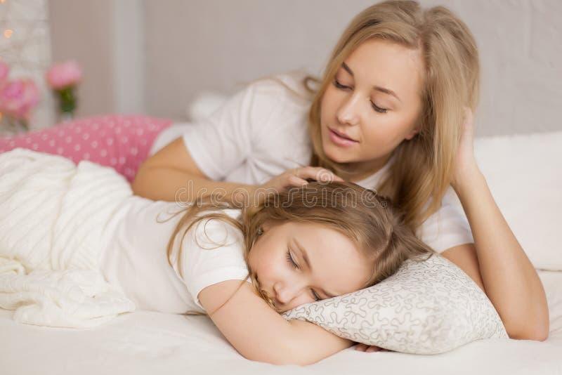 La mère a mis sa fille pour dormir Intérieur Soin de concept images libres de droits