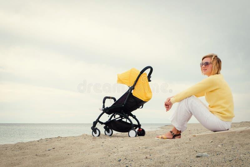 La mère obtient un certain repos sur la plage images libres de droits