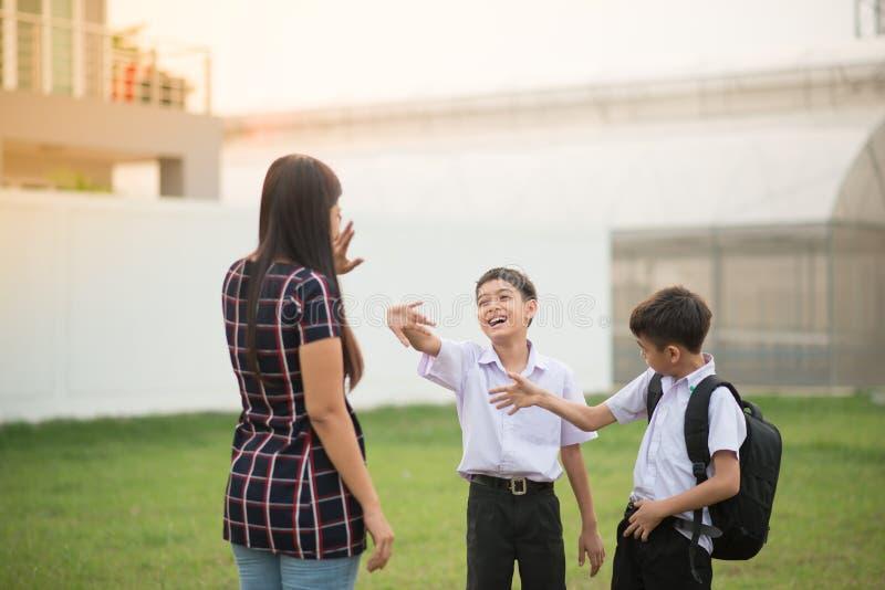 La mère portant des fils à l'école ensemble, vague de main disent au revoir photographie stock libre de droits