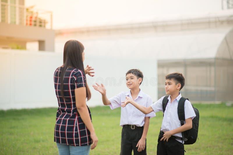 La mère portant des fils à l'école ensemble, vague de main disent au revoir images libres de droits