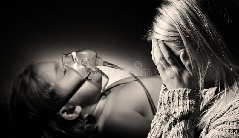 La mère prie pour la santé de la fille malade images stock