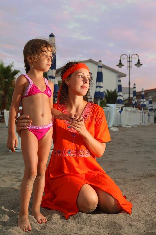 La mère s'assied sur la plage. le descendant est presque photo libre de droits