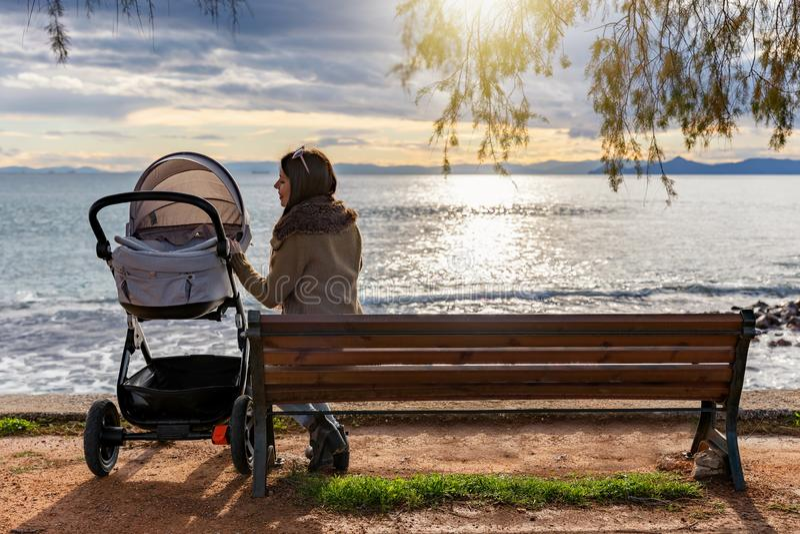 La mère s'assied sur un banc avec son bébé dans une poussette par la mer photo libre de droits