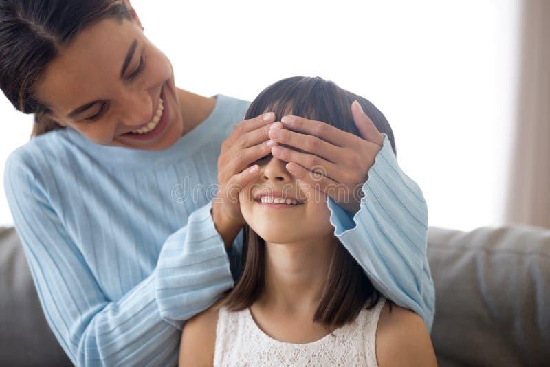 La mère se préparent à l'enfant que la surprise couvrent ses yeux de mains images stock