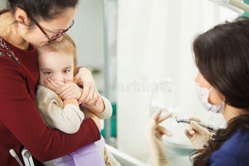 La mère tient l'enfant cet effrayé de l'examen par le dentiste photo libre de droits