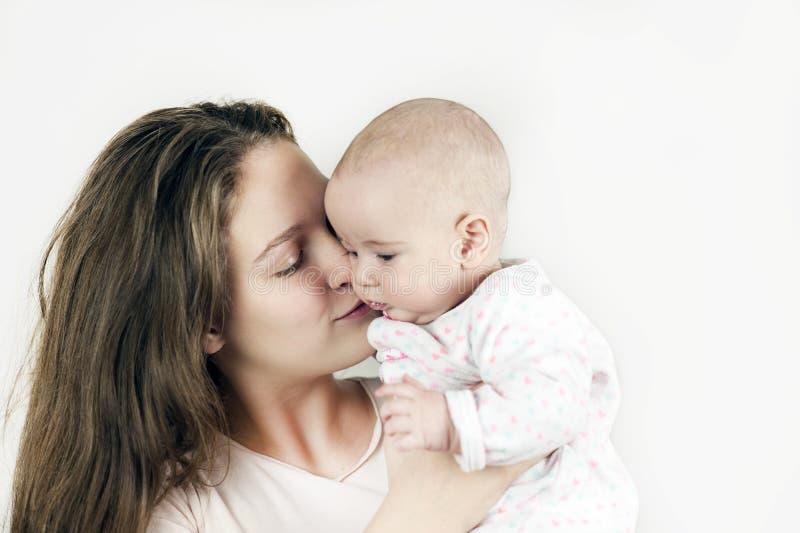 La mère tient le bébé dans des ses bras sur le fond d'isolement photos libres de droits
