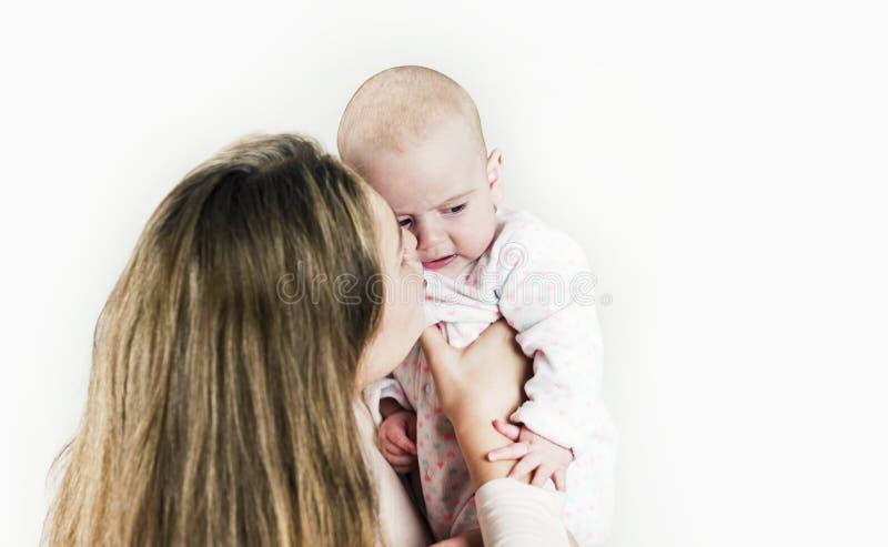 La mère tient le bébé dans des ses bras sur le fond d'isolement photo stock