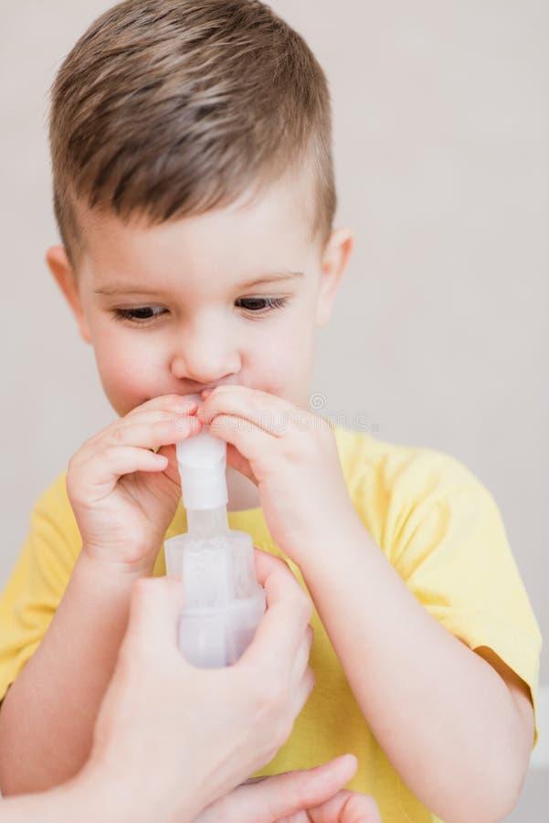 La mère traite la bronchite dans un enfant avec un nébuliseur photographie stock libre de droits