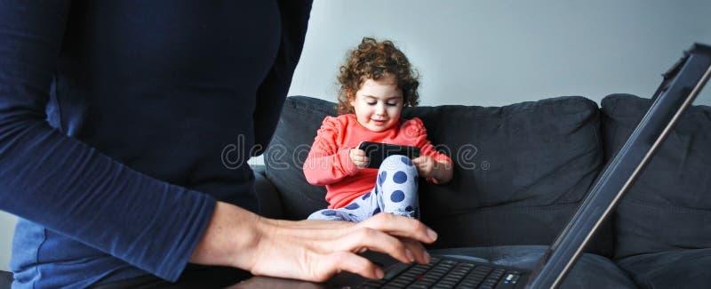 La mère travaille sur l'ordinateur portable tandis que ses jeux d'enfant sur le smartphone images libres de droits