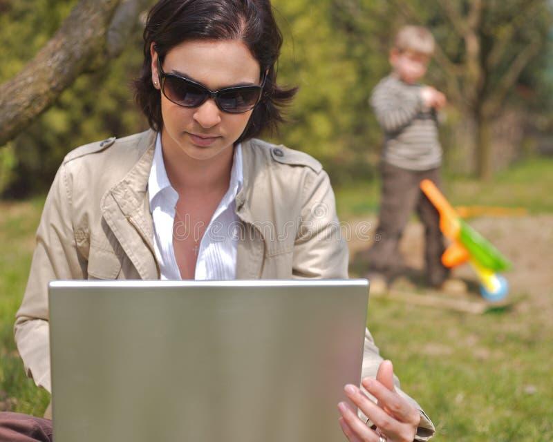 La mère utilise un ordinateur portatif image stock