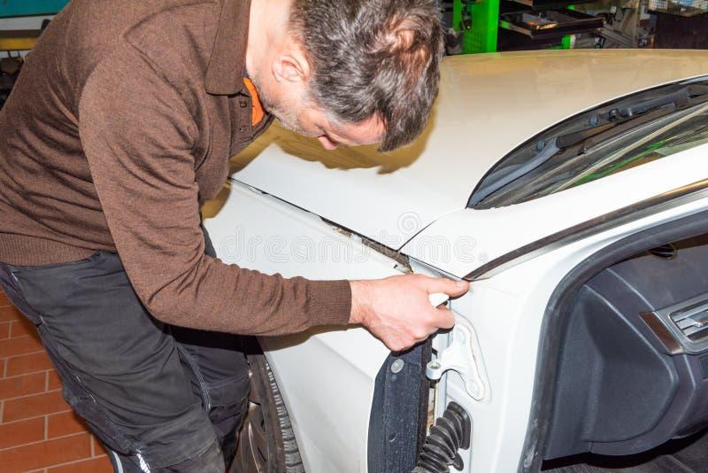 La mécanique de voiture aligne le capot correctement en se réunissant - atelier de réparation de Serie image libre de droits