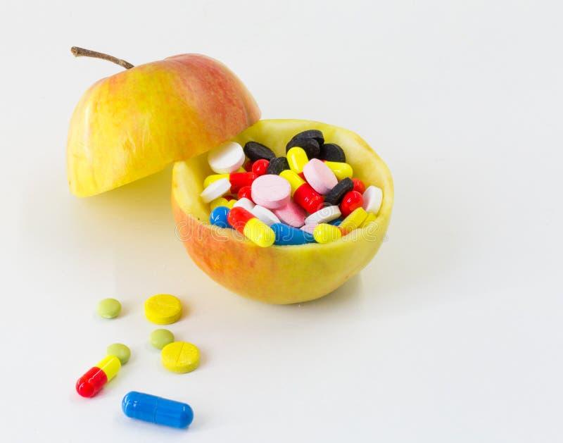 La médecine, pilules d'une couleur différente porte des fruits sur le fond blanc, santé de drogues photographie stock