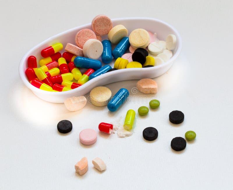La médecine, pilules de différentes couleurs sur un fond blanc, dope la santé photographie stock libre de droits