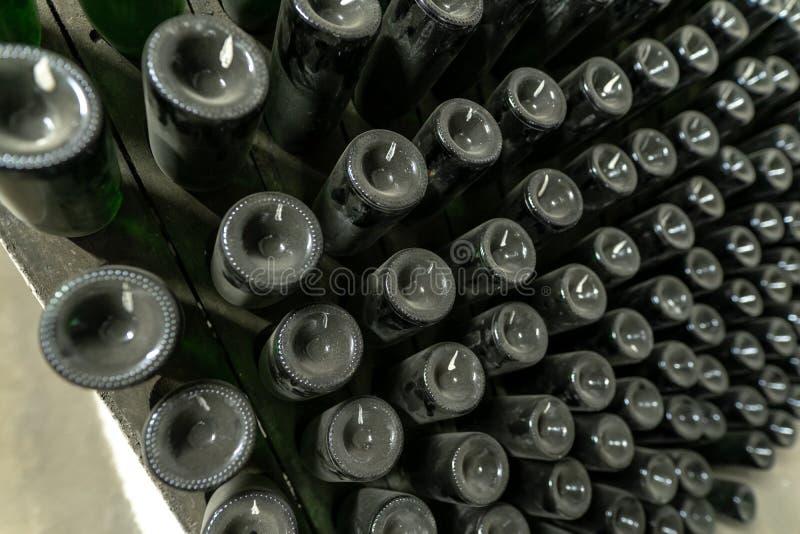 La méthode de la fabrication traditionnelle du vin mousseux avec les bouteilles de vin sur les supports en bois, a tourné quotidi photographie stock