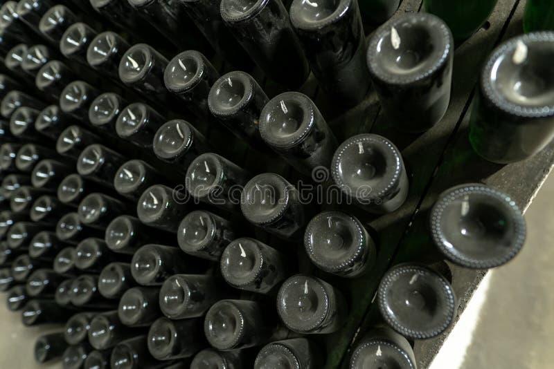 La méthode de la fabrication traditionnelle du vin mousseux avec les bouteilles de vin sur les supports en bois, a tourné quotidi photos stock