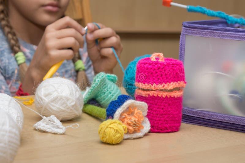 La métier-broderie des enfants se trouvant sur la table, à l'arrière-plan la fille tricote photos stock