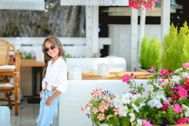 La m?re avec la petite fille avec du charme s'asseyent dans la terrasse d'?t? au soleil Ils sont ont le brunch Foyer sur photographie stock