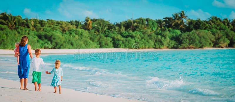 La m?re avec trois enfants marchent des vacances de plage photos stock