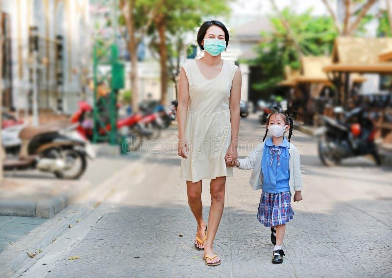 La m?re et sa marche de fille vont instruire avec porter un masque de protection contre P.M. 2 pollution 5 atmosph?rique dans la  image stock
