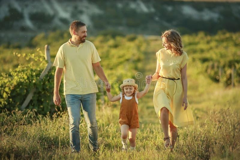 La m?re heureuse et le b?b? de famille ?treignant dans un pr? jaunissent des fleurs sur la nature en ?t? photographie stock