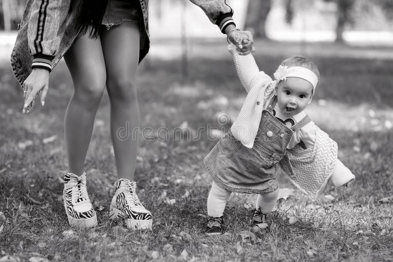 La m?re tient la main de sa fille une journ?e de printemps ? l'air frais, la famille marche en parc et s'amuse, noir et image stock