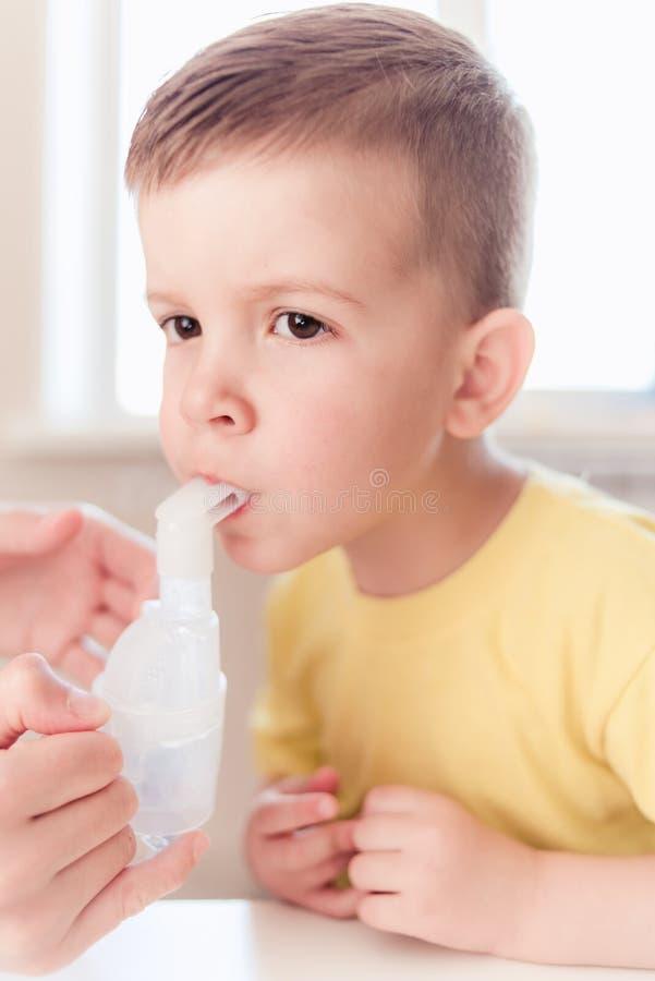 La m?re traite la bronchite dans un enfant avec un n?buliseur photo stock
