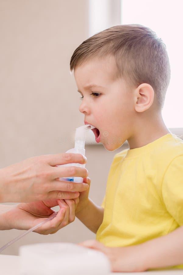 La m?re traite la bronchite dans un enfant avec un n?buliseur image libre de droits