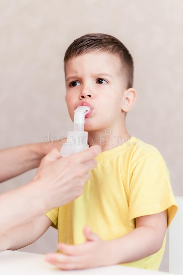 La m?re traite la bronchite dans un enfant avec un n?buliseur image stock