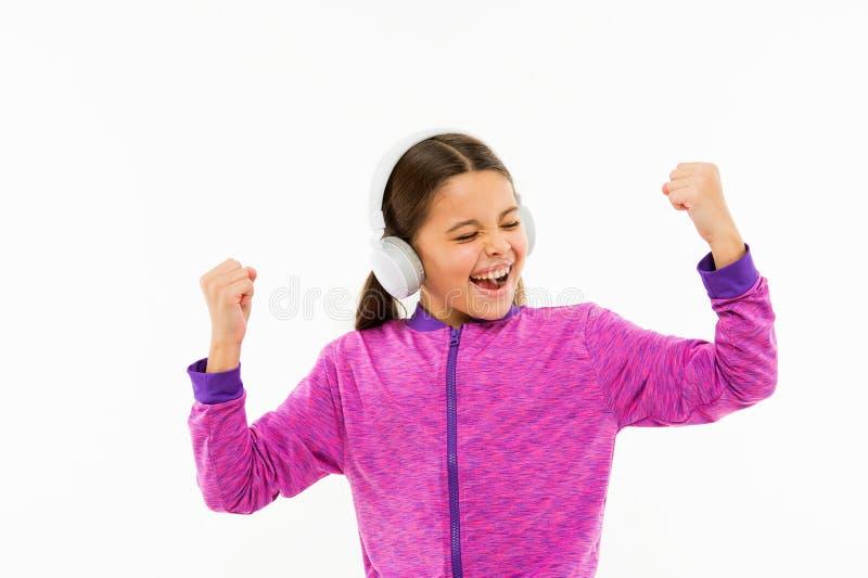 La m?sica es la mejor motivaci?n El ni?o activo disfruta de la m?sica que juega en los auriculares aislados en blanco Ni?o en?rgi imagenes de archivo