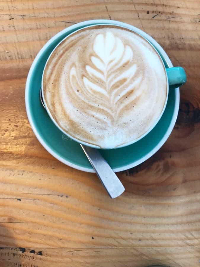 La mañana despierta bebiendo una taza de café con arte del café del modelo de la hoja de la espuma de la leche en la tabla de mad fotos de archivo