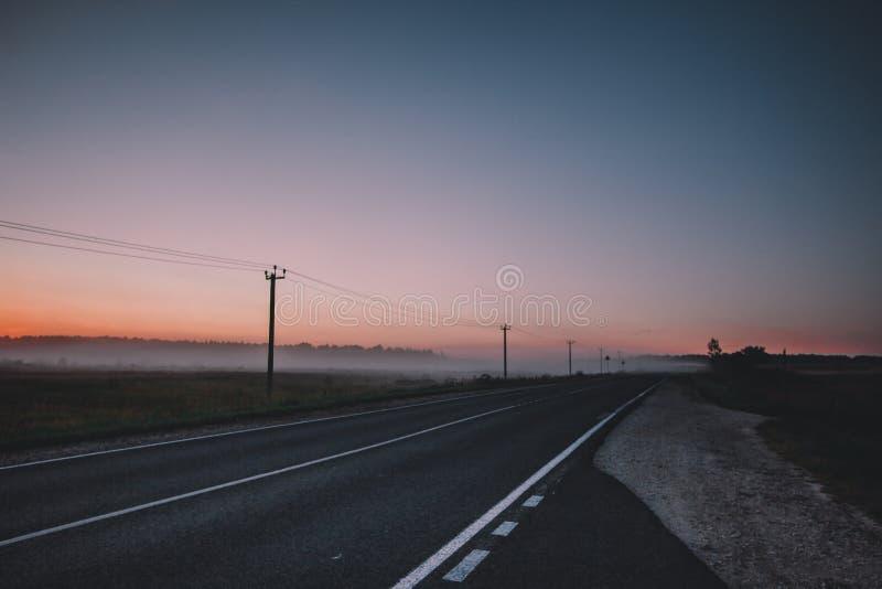 La mañana ha venido El sol anaranjado sube sobre un campo, una carretera de asfalto y un bosque brumosos, árboles oscuros fotos de archivo libres de regalías